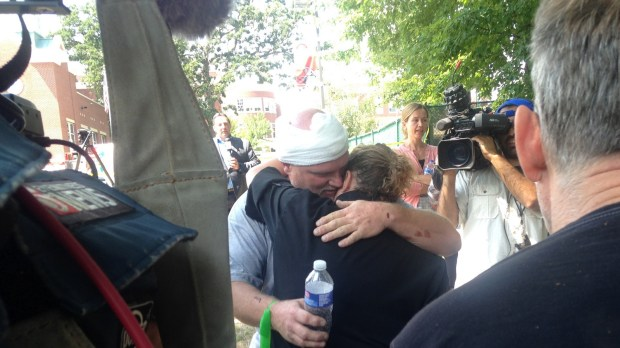 Upper Campus building supervisor Don DuBois gets a hug after being treated for his injuries after the blast at the school on Wednesday, Aug. 2, 2017. (Frederick Melo / Pioneer Press)