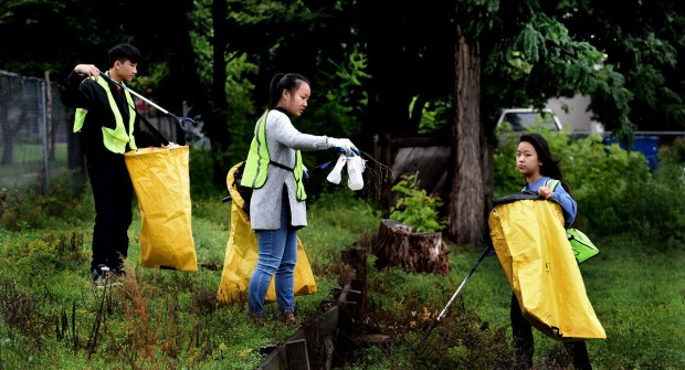 """From left, Nhia Vang, 16, a junior at Harding High School, Linda Xiong, 16, a junior at Central High School, and Amber Yang, 17, a senior at Roseville High School, and self-proclaimed """"Alley Advocates"""" pick up trash behind the Little Mekong Business District in St. Paul Friday, August 25, 2017. They are employed by the Asian Economic Development Association (AEDA) which pays them to pick up litter twice a week while learning about community leadership. The effort is supported by a two-year-grant from the Blue Cross and Blue Shield Foundation of Minnesota. The students completed mini-seminars on topics including financial literacy, college readiness and business etiquette.  (Jean Pieri / Pioneer Press)"""