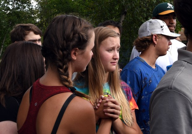 """Ashley Mullen, right, a recent graduate of Minnehaha Academy, clasps hands with a friend as officials brief the media on search and rescue efforts following a natural gas explosion at the private school in Minneapolis Wednesday, Aug. 2, 2017. """"I came when I heard the news,"""" she said. The friend declined to be identified. (Dave Orrick / Pioneer Press)"""