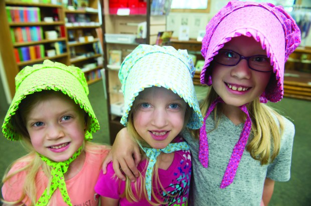Sisters Lyanna 5, Keira 5 and Arya, 7 (last name w/held at their request) visiting from Portland OR, picked out bonnets during their visit to the Laura Ingalls Wilder Museum where visitors come from all over the world to see the birthplace of the famous author and browse the museum. The museum is also home to a gift store that includes the author's books and, of course, bonnets in Pepin, Friday, August 11, 2017. (Special to the Pioneer Press: Craig Lassig)