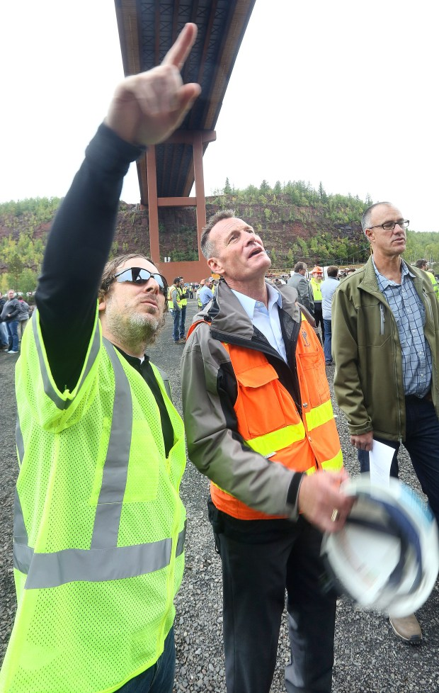 t9.15.17 Bob King -- 091617.N.DNT.HW53OPENc13 -- Nate Blanchard (left), who designed the roadway on the bridge, and bridge designer Vince Gastoni talk about the cabling that was used to protect the workers during the bridge's construction. Bob King / rking@duluthnews.com