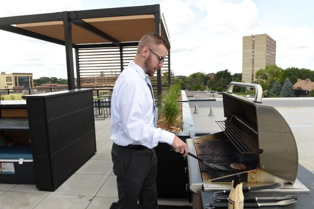 Jack Knutson, a 28-year-old banker, grills a burger on the rooftop patio of The Ray, a new apartment building in St. Paul's Midway area, on Wednesday, Sept. 6, 2017. Knutson has lived in a 372-square-foot apartment in the building since the end of July. (Scott Takushi / Pioneer Press)