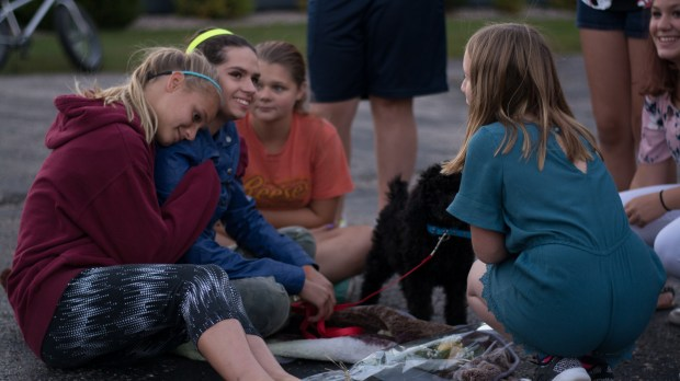 Jasmine Block, second from left, reconnects with friends, keeping her new service dog, Rocky, close by, during a community gathering to welcome Jasmine home. The event was set as a prayer service prayer service when Jasmine was still missing. With her return home after 29 days in captivity, it became a celebration. Three men have been charged in her abduction. (Beth Leipholtz | Forum News Service)