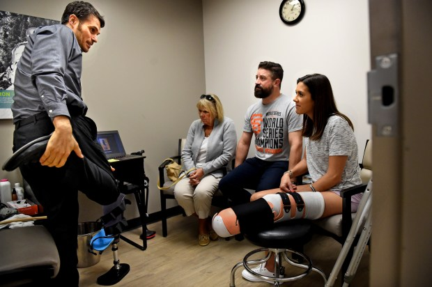 "Prosthetist Yakov ""Jacob"" Gradinar, left, talks to Courtney Godfrey, sitting by her husband, Ryan Novaczyk, and her mother, Barbara Godfrey, before he does casting for a temporary bent-knee prosthesis at Hanger Clinic in Minneapolis Friday, Sept. 29, 2017. Godfrey lost her lower leg following a boating accident Sept. 15. (Jean Pieri / Pioneer Press)"
