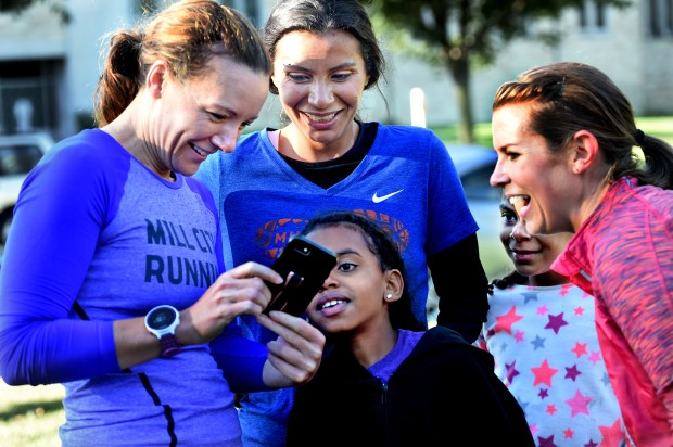 Mile in My Shoes program director, Mishka Vertin, left, shows cell phone running photos to Nour Tamimi, her children, Yasmin, 7, center, and Doniah, 8, and Nour's running mentor, Anne Rauch after a workout in St. Paul Wednesday, Sept. 27, 2017. Tamimi, a refugee, will be running the Twin Cities Marathon for the first time this year. She is a participant in Mile in My Shoes, a program that helps homeless and disadvantaged people take up running.  (Jean Pieri / Pioneer Press)