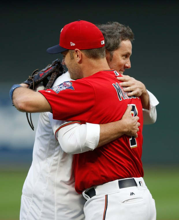 Former Minnesota Twins pitcher Joe Nathan, right, and Twins' Joe Mauer hug after Mauer caught the ceremonial first pitch shortly after Nathan, the team's closer, signed a one-day contract to announce his retirement from baseball, prior to the Twins' game against the Kansas City Royals on Friday, Sept, 1, 2017, in Minneapolis. (AP Photo/Jim Mone)