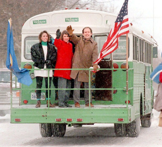 Paul and Sheila Wellstone, along with their daughter Marcia (left), wave goodbye on Dec. 30, 1990, at the beginning of their trip to Washington, D.C., in the battered school bus that came to symbolize Wellstone's personality and politics. (Pioneer Press)