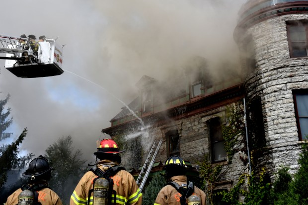"""St. Paul firefighters battle a large blaze Tuesday, Oct. 10, 2017 at a home in the 200 block of Dayton Avenue in St. Paul. Built in the 1800s, the Cathedral Hill home was extensively damaged. Two cats died in the fire, but no other injuries were reported. Firefighters were called to a """"very, very large house on fire"""" across from the Cathedral of St. Paul at 11:34 a.m. Tuesday, said St. Paul Fire Marshal Steve Zaccard. (Trevor Squire / Pioneer Press)"""