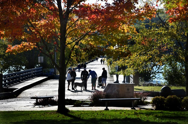 People walk the pier in Hudson, Wisconsin Friday, Oct. 13, 2017. Some redesign options are being considered to better connect the park near the waterfront with downtown areas in Hudson, Wisconsin. (Jean Pieri / Pioneer Press)