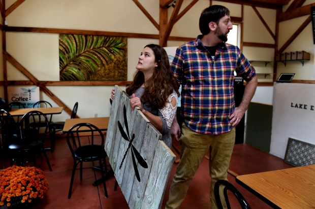 Sarah Marshall and her husband Paul, two of the four co-owners, look around and try to figure out where they should hang dragonfly art at Lake Elmo Coffee on Thursday, Oct. 12, 2017. The city has spent millions to attract new businesses to the historic downtown area, and this coffee shop is the first retail business, and a sign that the strategy is working. The other co-owners are Sarah's parents, Bill and Sue Lockwood. (Jean Pieri / Pioneer Press)