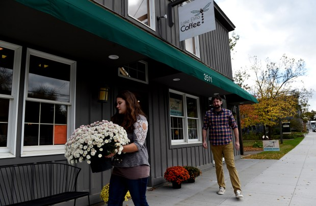 Sarah and Paul Marshall place four pots of flowers outside at Lake Elmo Coffee on Thursday, Oct. 12, 2017. The city has spent millions to attract new businesses to the historic downtown area, and this coffee shop is the first retail business, and a sign that the strategy is working. (Jean Pieri / Pioneer Press)