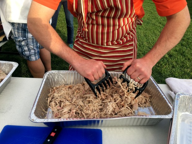 Ryan Fleming shreds the pig meat with plastic claws made for shredding in Cottage Grove on Saturday, Sept. 30, 2017. (Jessica Fleming / Pioneer Press)