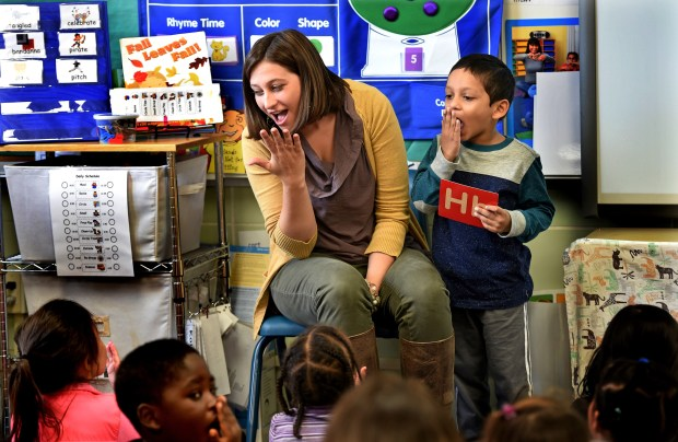 "Teacher Julie Heroff and student Mannan Asif show a preschool class at Castle Elementary School in Oakdale how to make the ""H"" sound by blowing the sound on their hands on Wednesday, Oct. 11, 2017. ""It's a tactile, hands-on approach,"" said Heroff. ""It helps them make that sound."" (Jean Pieri / Pioneer Press)"