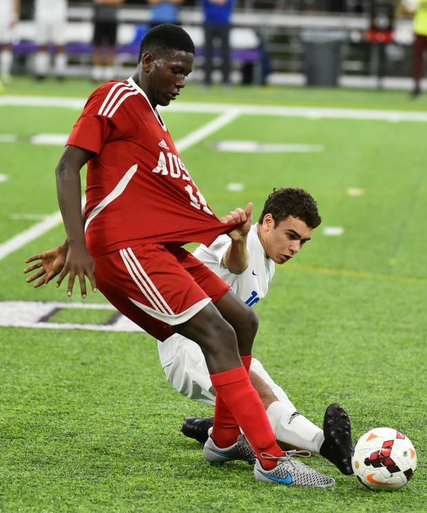 St. Thomas Academy m Davis, Logan hangs on to Austin d Ojulu Cham shirt as he kicks the all away in the second half of a Class A semifinal game of the State Boys Soccer Tournament at U.S. Bank Stadium in Minneapolis, Monday Oct 30, 2017. (John Autey / Special to the Pioneer Press)