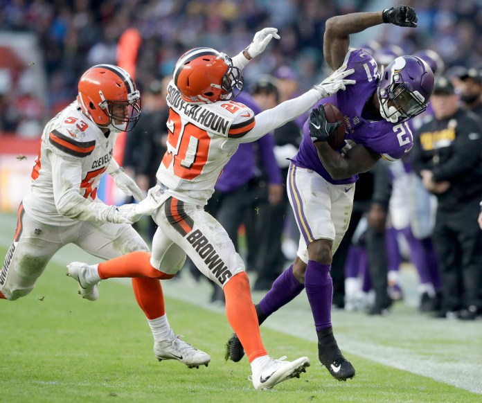 Minnesota Vikings running back Jerick McKinnon, right, runs with the ball before being pushed out of bounds by Cleveland Browns safety Briean Boddy-Calhoun (20) as Browns linebacker Joe Schobert, left, watches during the second half of an NFL football game at Twickenham Stadium in London, Sunday Oct. 29, 2017. (AP Photo/Matt Dunham)