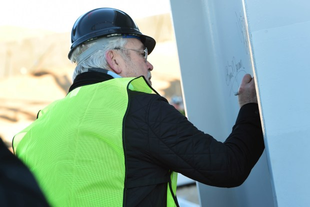 Dr Bill McGuire, owner of the Minnesota United Football Club signs a steel column before it is raised by a crane and moved into place during a ceremony Tuesday, November 21 at the Allianz Field stadium site in St. Paul, Nov. 21, 2017. (Scott Takushi / Pioneer Press)