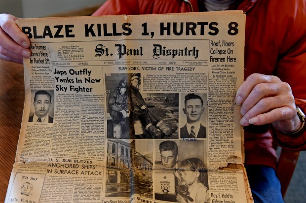 Walter Holm, Wednesday, Nov. 22, 2017, shows the June 4, 1945 St. Paul Dispatch front page stories and photos of the fire his brother, Milford Holm, lost his life in. (Jean Pieri / Pioneer Press)