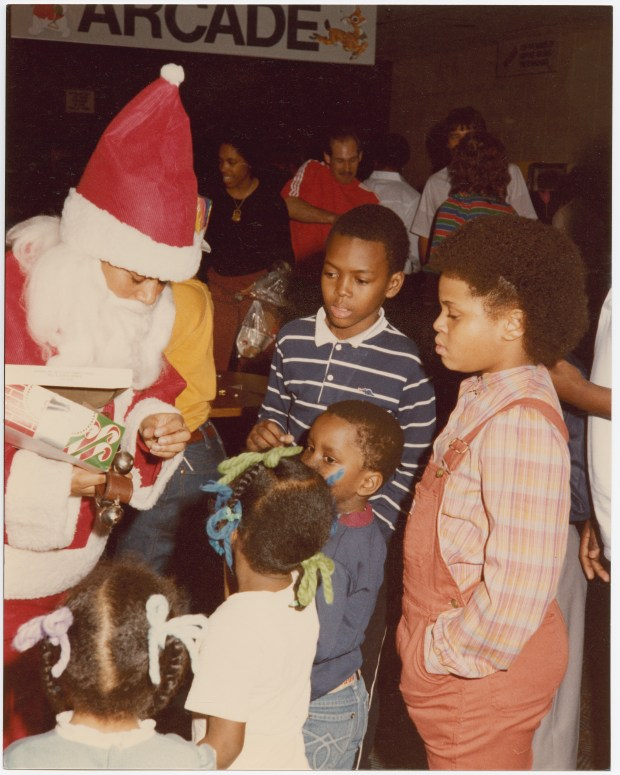 """A black Santa Claus meets children. (Image from """"Sights, Sounds, Soul: The Twin Cities Through the Lens of Charles Chamblis"""")"""