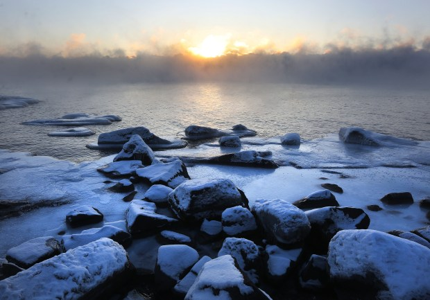 The rising sun colors the fog over Lake Superior in warm tones that contrasts with the chill blue of ice-coated rocks along the shore of Brighton Beach Wednesday morning, Dec. 27, 2017. (Bob King / Forum News Service)