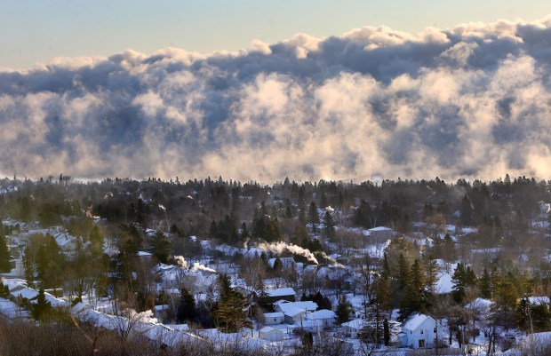"t12.26.17 Bob King -- 122817.N.DNT.COLDc6 -- A wall of ""sea smoke"" on Lake Superior towers above Duluth's Lakeside neighborhood Wednesday morning as the temperature dips to 21 below zero. Cold air causes the water in the warmer air over the lake's surface to condense out as fog. Bob King / rking@duluthnews.com"