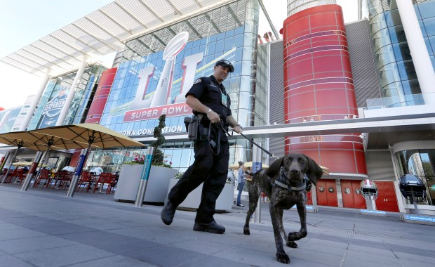 Officer Keith McCart, of the Long Beach, Calif. Police Department, patrols with K-9 Pidura outside the George R. Brown Convention Center, the NFL Super Bowl 51 football media center and site of the NFL Experience, Tuesday, Jan. 31, 2017, in Houston. (AP Photo/David J. Phillip)
