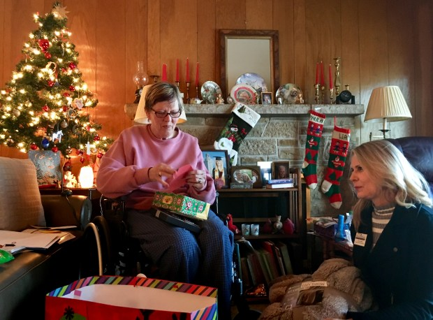 "Paula Amundson of St. Paul opens a gift from ""Santa,"" delivered by Tracy Allen, lead client care coordinator, at her St. Paul home on Friday, Dec. 22, 2017. Paulson was nominated by someone from the community, and an anonymous donor picked out gifts for her, as part of the Santa to a Senior program that Home Instead runs. (S. M. Chavey / Pioneer Press)"
