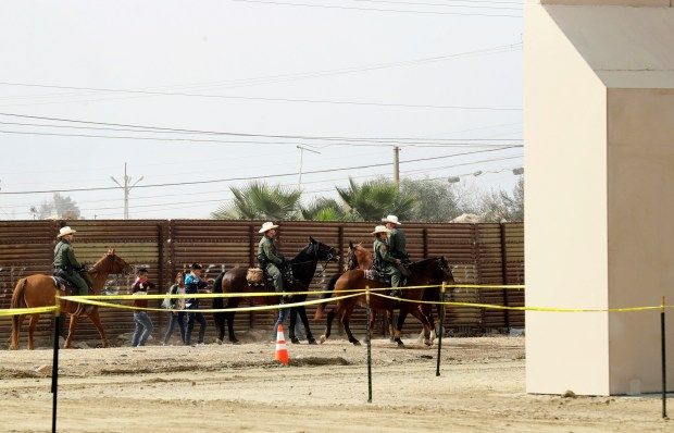 FILE - In this Oct. 19, 2017, file photo, a group of people are detained by Border Patrol agents on horseback after crossing the border illegally from Tijuana, Mexico, near prototypes for a border wall, right, being constructed in San Diego. The federal government provided Tuesday, Dec. 5, 2017, the most complete statistical snapshot of immigration enforcement under President Donald Trump, showing Border Patrol arrests plunged to a 45-year low while arrests by deportation officers soared. (AP Photo/Gregory Bull, File)
