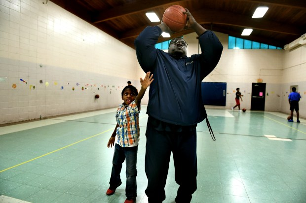 """Donntrell Mathews, 7, left, guards against Eric Brown, a rec leader for the City of St. Paul on the basketball court at Scheffer Recreation Center in St. Paul on Thursday, Dec. 14, 2017. """"Can't wait for it (the new building) to be here in the community,"""" said Brown. He said the small basketball court isn't big enough to have official games held on it. St. Paul's newest giant recreational facility will be 23,500 square feet and will replace the aging 6,600 square foot structure in Frogtown. (Jean Pieri / Pioneer Press)"""