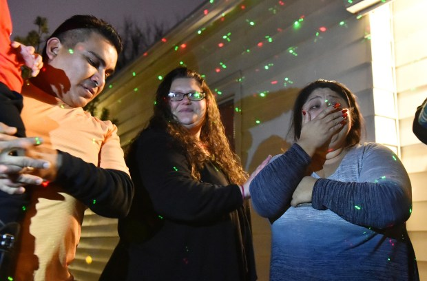 LeeAnn Larson, center, stands with Clarissa Benitez, left, and Victor Benitez as over 120 community members sing Christmas Carols and deliver presents the East Side Saint Paul Family on Thursday, Dec. 21, 2017. Clarissa lost her 16 year-old son, a Harding High School student after he fell ill. Larson organized the event. (Pioneer Press / John Autey)