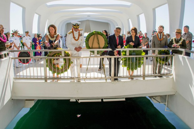 Adm. Scott Swift, left center, along with his wife and Gov. David Ige, right center, and his wife Dawn Amano Ige throw orchids into the waters of the Arizona Memorial in Honolulu, during a ceremony commemorating the 76th anniversary of the attack on Pearl Harbor. (Dennis Oda /The Star-Advertiser via AP, Pool)