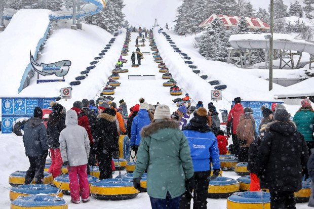 Visitors to Valcartier Winter Park wait to ride the inner tube lift. Just plop down and belts will take you to the top. (Brian Sirimaturos/St. Louis Post-Dispatch/TNS)