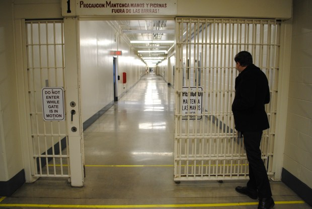 Tribune file/ Jonathan Burns, with CoreCivic, peers through a gate at a housing area in the Prairie Correctional Facility during a 2016 tour of the shuttered facility. An architectural assessment has been completed for the legislature that provides costs for the state to purchase, upgrade and staff the prison, or to lease it.