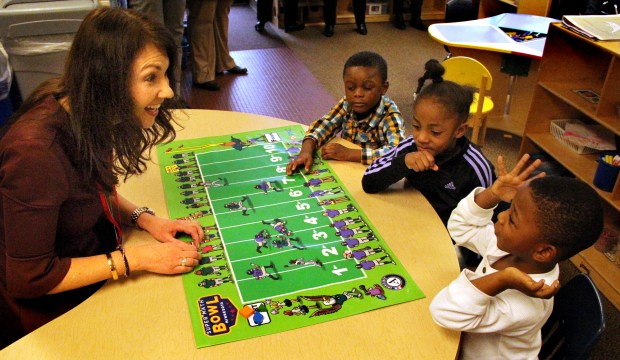Deb Rohloff, PNC community relations director, plays a math game Jan. 10, 2018 with students from the Wilder Foundation Child Development Center in St. Paul. Students from bottom are: Na' Rann Barnes, Na' Lyzah McCrimman and Ezra Yeboah. (Christopher Magan / Pioneer Press)