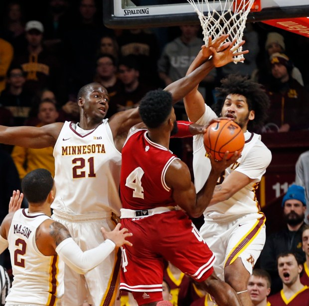 Indiana's Robert Johnson (4) lays up as Minnesota's Bakary Konate, left, and Jordan Murphy defend in the second half of an NCAA college basketball game Saturday, Jan. 6, 2018, in Minneapolis. Illinois won 75-71. Johnson led Illinois with 28 points. (AP Photo/Jim Mone)