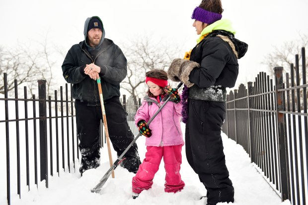 Four-year-pld Kyra Bauer helps her parents Shawn, left, and Meghan dig through the snow as the Maplewood family searches for the Pioneer Press Treasure Hunt medallion in Mounds Park in St. Paul on Wednesday, Jan 24, 2018. (John Autey / Pioneer Press)