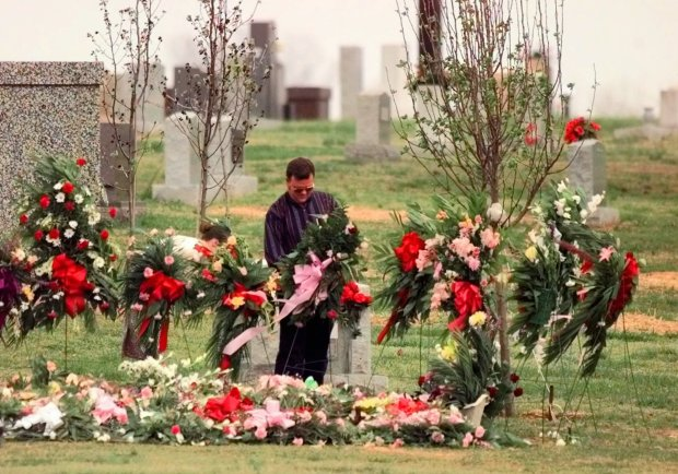 Unidentified family members adjust flowers at the grave site of Shannon Wright, Sunday, March 29, 1998, in Jonesboro, Ark., the day after she was buried. Wright, a teacher, and four students were shot to death by two students at Westside Middle School, Tuesday. Pastors urged forgiveness Sunday and praised the hundreds of behind-the-scenes helpers who have given their time, talents and treasures after a deadly school shooting shattered the morale of many in this community. (AP Photo/J. Pat Carter)