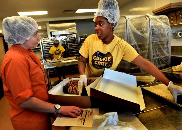 Amani MccGee, 17, right, talks to production manager Beth Leasman about an order for seven dozen cookies she is filling at Cookie Cart in Minneapolis on Thursday, Feb. 14, 2018. She is in a youth training program and learning all aspects of cookie production. (Jean Pieri / Pioneer Press)