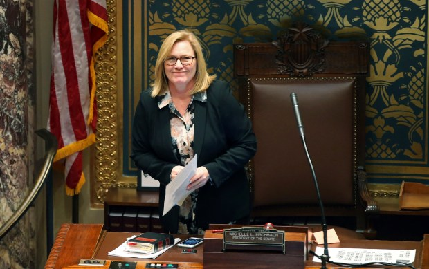 Senate President Michelle Fischbach smiles at photographers in the gallery prior to convening the Minnesota Senate as the 2018 legislative session got underway Tuesday, Feb. 20, 2018, in St. Paul, Minn. Fischbach is trying to keep her Senate seat in a dual role since becoming lieutenant governor earlier this year to replace then-lieutenant governor Tina Smith who was named to the U.S. Senate. (AP Photo/Jim Mone)