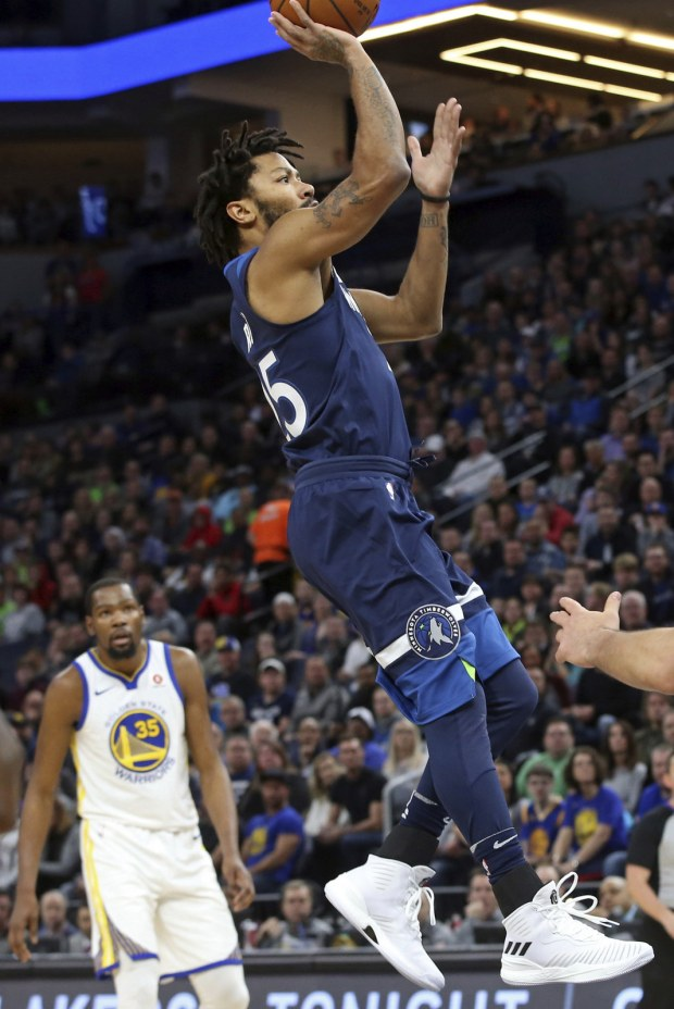 Minnesota Timberwolves' Derrick Rose, right, shoots as Golden State Warriors' Kevin Durant, left, looks on as Rose made his playing debut with the Timberwolves in the first half of an NBA basketball game Sunday, March 11, 2018, in Minneapolis. (AP Photo/Jim Mone)