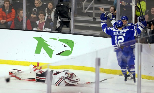 St. Cloud State goalie David Hrenak (34) falls to the ice as Air Force's Matt Serratore (12) celebrates an Air Force goal with a teammate during the third period of an NCAA regional men's college hockey tournament game Friday, March 23, 2018, in Sioux Falls, S.D. (AP Photo/Dave Eggen)