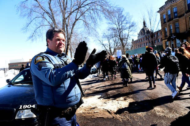 St. Paul Police Sgt. Mike McGinn claps as students from across the Twin Cities marched by on Marshall Avenue on their way to the Minnesota State Capitol in St. Paul to demonstrate against gun violence Wednesday, March 7, 2018. He said his brother is a SRO (school resource officer) at Harding who helps keep the students safe. (Jean Pieri / Pioneer Press)