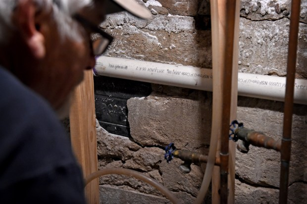 Burnell Brown shows a battery inside the foundation of the old utility and furnace room in the basement of his White Bear Lake home on April 25, 2018. He estimates there are 1,000 batteries in the walls, now mostly all covered up by his remodeling. (Jean Pieri / Pioneer Press)