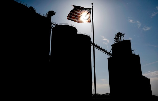 A flag flies over the Heartland Co-op grain elevator, Thursday, April 5, 2018, in Dallas Center, Iowa. The trade dispute with China is threatening to rattle small-town economies and election-year politics. Just seven months before the 2018 midterm elections, Trump's faceoff with China over trade has exposed an unexpected political vulnerability in what was supposed to be the Republican Party's strongest region: rural America. (AP Photo/Charlie Neibergall)