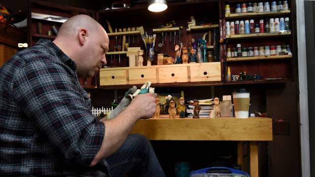 Tanner Spicer carves a wood figure in his garage in Chisago City, Friday, April 20, 2018. 'I find it very relaxing,' he says of his self-taught hobby. But for the veteran Mendota Heights cop, it also provides him a source of calm and solace following a summer day in 2014 when he was one of the first responders when his co-worker, officer Scott Patrick, was fatally shot during what was supposed to be a routine traffic stop. (Jean Pieri / Pioneer Press)