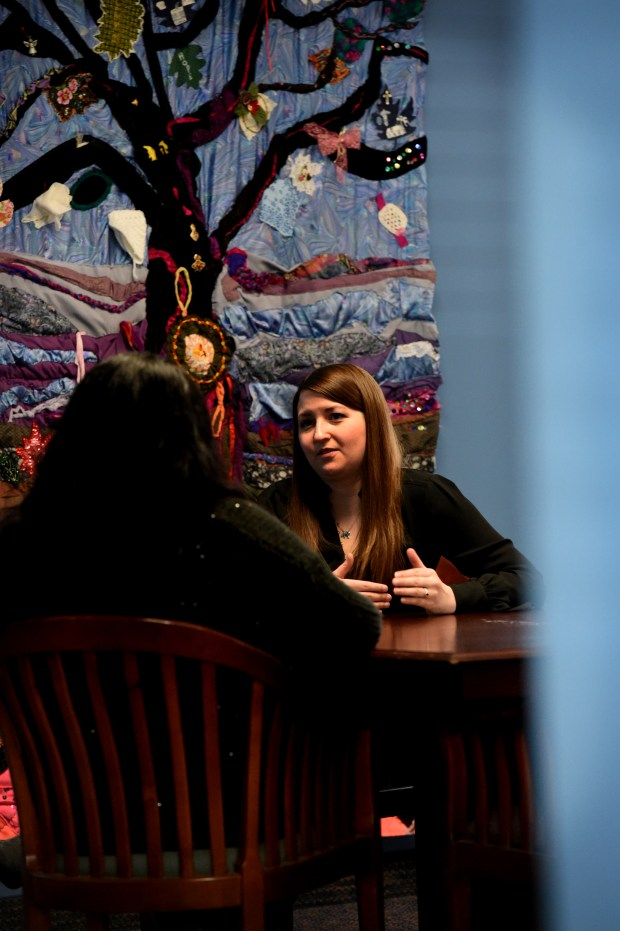 Charlotte, left, a domestic abuse survivor, talks with Abby S., a legal advocate with St. Paul Intervention Project, in St. Paul Thursday, April 5, 2018. Charlotte has never been homeless and she considers herself fortunate because she knows that other women have trouble finding housing after domestic abuse. In the background is a quilt made by the elder women support group, who created patches for the tree which reflect where they're at in their healing or where they want to be. (Jean Pieri / Pioneer Press)