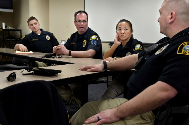 St. Paul Police Mental Health Program Coordinator, Jamie Sipes, second from left, huddles midday with St. Paul Police mental health officers, from left, Justin Tiffany, Lori Goulet and Titus Marshall at headquarters in St. Paul on Wednesday, March 14, 2018. Last year the mayor agreed to add four new officers to the St. Paul police budget for 2018 to form a mental health unit. (Jean Pieri / Pioneer Press)