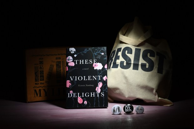 """A recent My Lit Box includes """"These Violent Delights,"""" by Victoria Namkung, along with pins and a Resist tote bag. Katherine Frey / Washington Post)"""