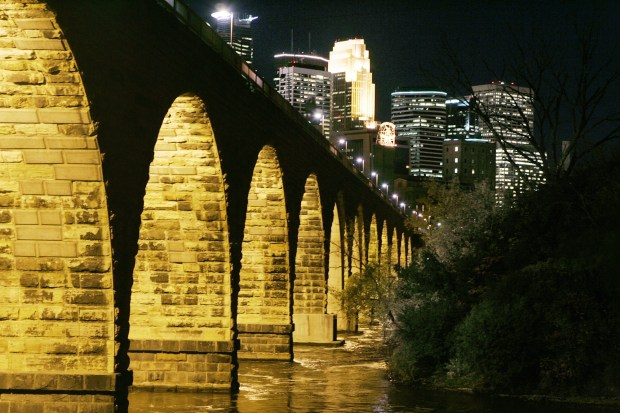The Minneapolis skyline is seen in the background after the historic 122-year-old Stone Arch Bridge over the Mississippi River was lit in a ceremony Monday, Oct. 17, 2005. Money for the project to light 12 of the bridge's 21 arches was raised through private donations. (AP Photo/Jim Mone)