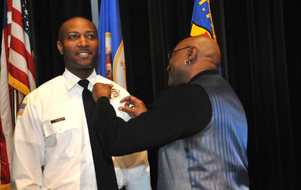 DuJuan Williams left, has his badge pinned on by his uncle Darryl Williams as 19 new St. Paul firefighters graduated from the city's Firefighter Academy during a ceremony at the Paul and Sheila Wellstone Center in St. Paul on Friday, May 11, 2018. (Ginger Pinson / Pioneer Press)