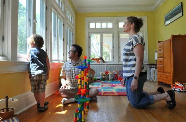 Wendy Caucutt, right, and her husband, George, look out the windows with their son, Kyle, 3, in the sunroom of their Summit Avenue home in St. Paul on Wednesday, May 16, 2017. In 2014, the couple wanted to swap out nine pairs of interior swinging window casements custom-ordered replacement windows. The city's Heritage Preservation Commission rejected the request saying the proposal was a threat to the their home's historic architecture. The St. Paul City Council reversed the decision in her favor. (Ginger Pinson / Pioneer Press)